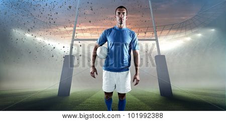 Portrait of rugby player looking away while holding ball aside against rugby stadium
