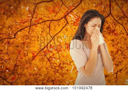 Sick brunette blowing her nose against autumn scene