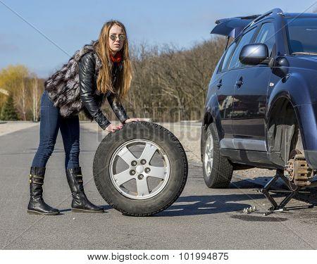 Female driver repairs car
