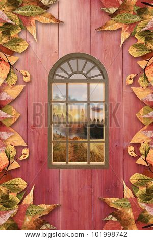 Digitally generated image of arch window against autumn leaves on wood