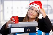 Young Woman In Santa Hat Exhausted In Office