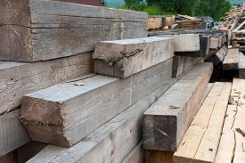 picture of rafters  - wooden rafters evenly stacked to be used to build a roof truss - JPG