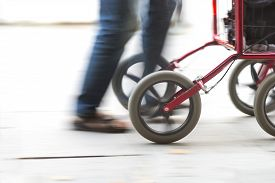image of rollator  - Feet of elderly person with red walking frame in blurred motion - JPG