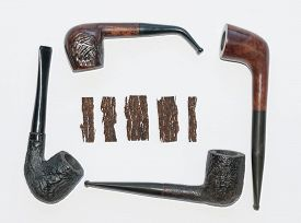 foto of tobacco-pipe  - four old wooden smoking pipes and pieces of pressed tobacco close - JPG
