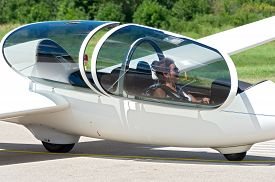 stock photo of glider  - glider or sailplane passenger seated in cockpit waiting for takeoff from runway - JPG