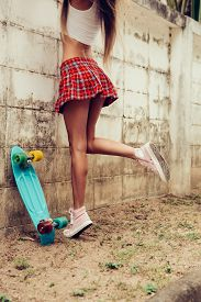 stock photo of mini-skirt  - Close up of a young girl with sporty ass in a red tartan mini skirt with blue penny skateboard trying to climb over the fence of a tropical garden - JPG