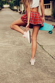 foto of mini-skirt  - Skinny young lady in a sexy red tartan mini skirt hold her blue penny skateboard shortboard while stands on the tropical street and touch her sneakers - JPG