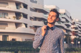 picture of bow tie hair  - Young handsome man with short hair wearing a bow tie and posing in the city streets - JPG