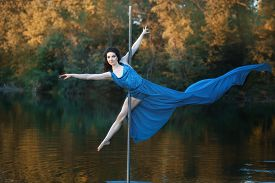 stock photo of lap dancing  - Girl in a flowing dress is dancing around a pole dance. Outdoors on the river.