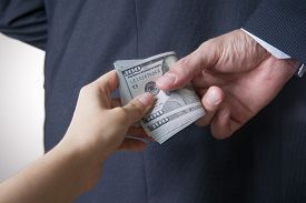 stock photo of corruption  - Businessman with money in studio on a gray background - JPG