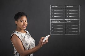 image of swot analysis  - South African or African American black woman teacher or student holding a tablet with a SWOT analysis standing against a chalk blackboard background inside - JPG