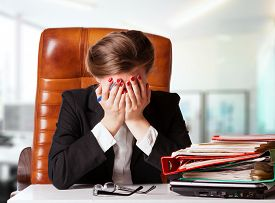 foto of disappointed  - Portrait of mature disappointed businesswoman sitting at desk in office - JPG