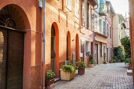 stock photo of paint pot  - Low afternoon sun illuminating narrow old street with colorful painted buildings and green potted plants in medieval town Villefranche - JPG