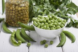 picture of pea  - Fresh green peas in a white bowl canned peas in a glass jar and some pea pods on a white table - JPG