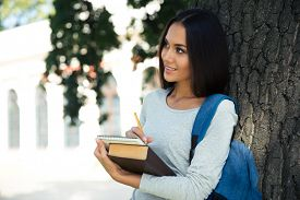 picture of thoughtfulness  - Portrait of a thoughtful female student standing and looking away outdoors - JPG