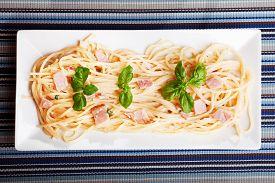 picture of carbonara  - Spaghetti carbonara decorated with fresh basil leaves - JPG