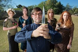 stock photo of priest  - Serious male pagan priest with group and dagger outdoors - JPG