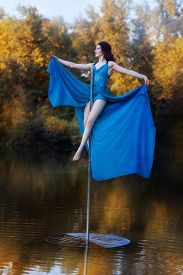 pic of lap dancing  - Girl in a blue dress sits high on a pole dance - JPG