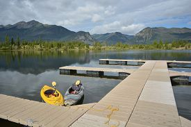 picture of dock a lake  - A pair of floating kayaks at a dock on a reflecting mountain lake - JPG