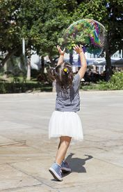 stock photo of hughes  - Three years old girl playing in the city with a huge bubble
