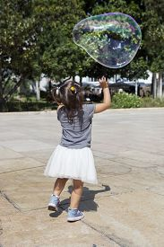 stock photo of hughes  - Three years old girl playing in the city with a huge bubble - JPG