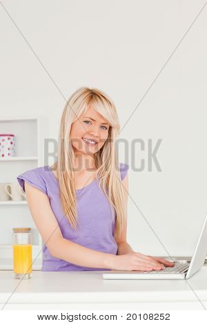 Beautiful Female Relaxing On A Laptop In The Kitchen