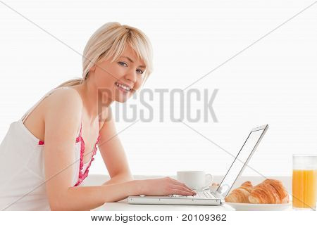 Beautiful Smiling Female Having Her Breakfast While Relaxing With A Laptop