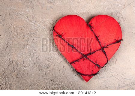 Barbed wire wound around a red heart on a grungy background