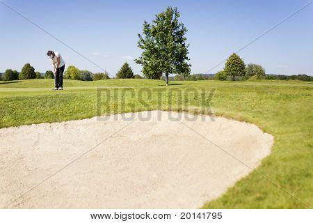 Active senior female golf player putting golf ball on green on beautiful golf course with sand bunker in foreground.