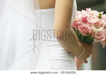 a classic bride poses with pink flowers