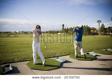 golf swings at the practice range