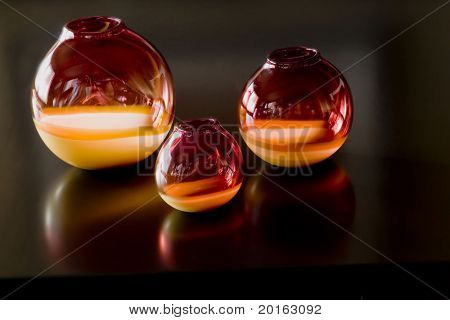 hand blown glass jars on chocolate coffee table with reflection