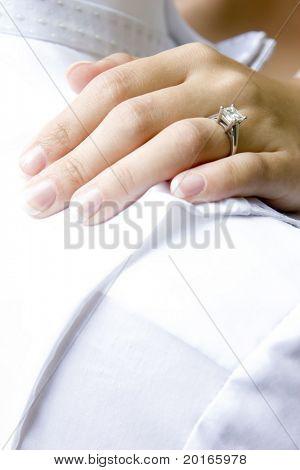 bride's hand resting on shoulder of groom diamond showing
