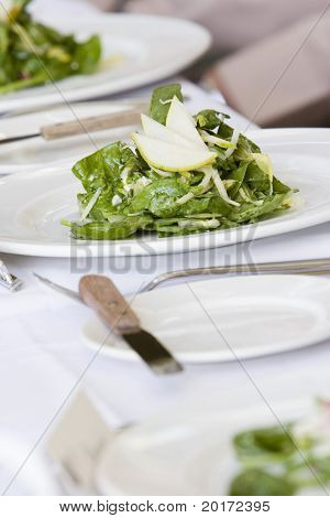 formal place settings of salad on white plates