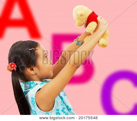 Girl Holding Her Teddy Bear Up In The Air