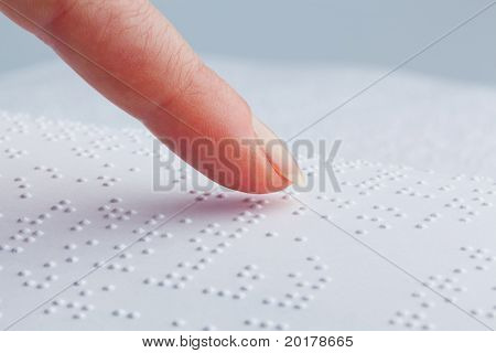 Braille and finger. Book in Braille