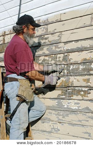 Man Scrapping Paint from House