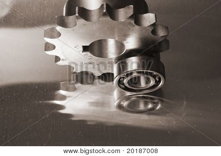 gears/cogs and smaller ball-bearing reflecting in titanium