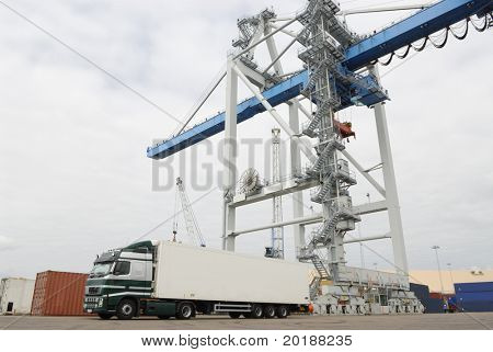 truck, lorry waiting for cargo from crane in shipping port