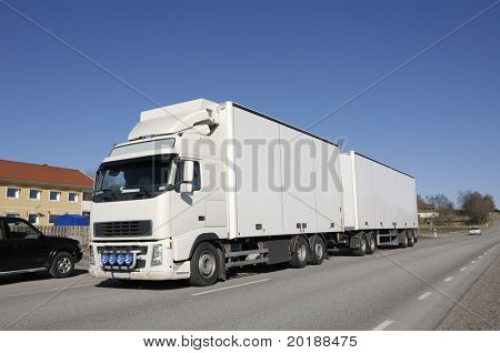 clean white truck driving on country-road, houses and cars