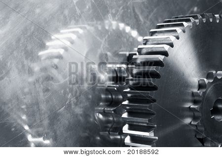 two large gears mirrored in steel and in a dark bluish toning