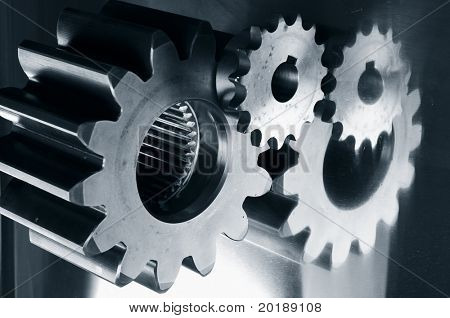 gears mechanical parts mirrored in steel and in a dark duplex greenish toning