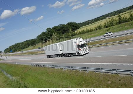 clean white truck on highway with field and forrest in background