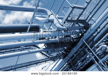 blue toned pipelines against blue sky, inside oil-refinery exterior