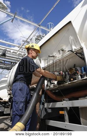 engineer attaching pipeline nozzle inside oil-refinery awaiting oil tanker