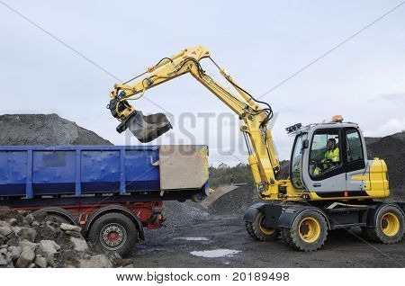 digger, bulldozer filling up waiting truck with sand and stone