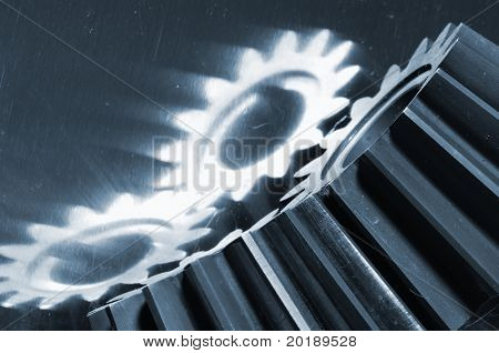 two gears reflecting in steel background and in a bluish toning idea
