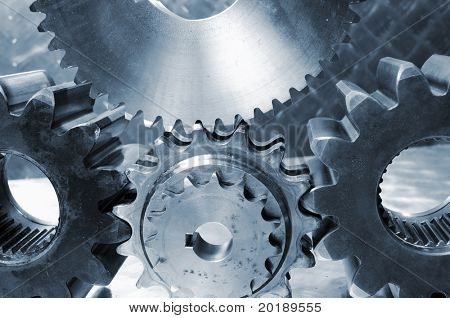 five industrial gears as a machinery against titanium background and in blue toning idea