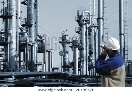 engineer in hard-hat pointing at oil and gas industrial plant