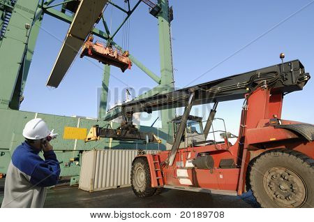 large forklift truck lifting containers in port, port-worker in hard-hat supervising on the phone